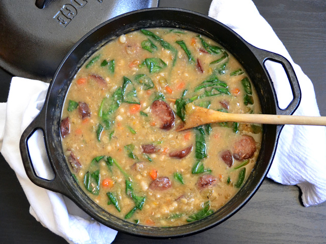 Overhead view of Navy Bean Soup with Sausage and Spinach in a cast iron pot with a wooden spoon