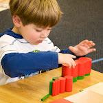 Preschool boy in Irvine Montesori school working with knobless cylinder sensorial material.