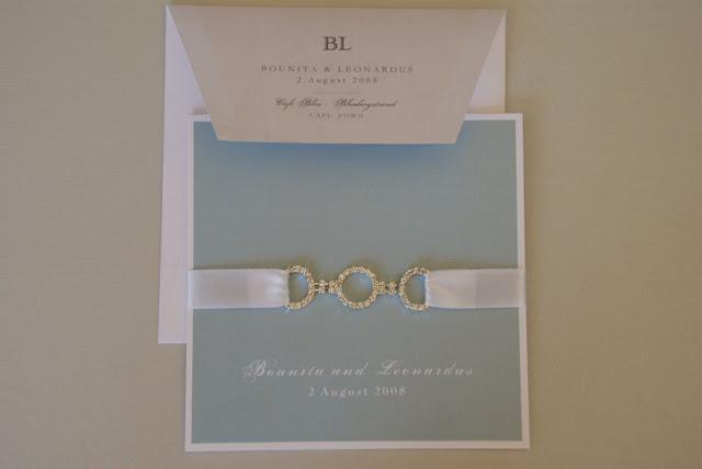 Invitación celeste con broche para boda
