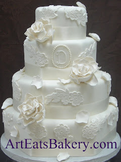 Four tier round and hexagon modern custom wedding cake with flower lace, sugar roses, rose petals, monogram, pearls and ivory ribbons design