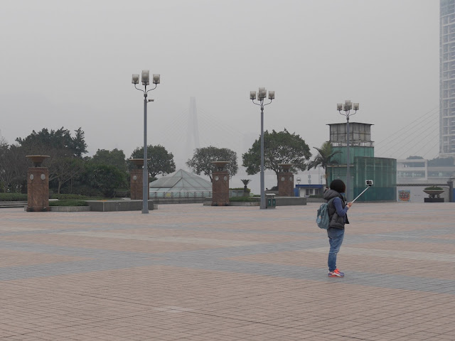 young woman using a selfie stick at Chaotianmen Square