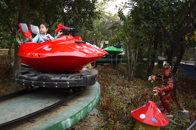 Girl on railed amusement park ride with fake guns in Zhuhai, China