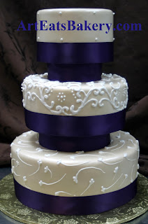 Three tier champagne pearl fondant custom wedding cake with white royal icing designs and blue ribbons idea