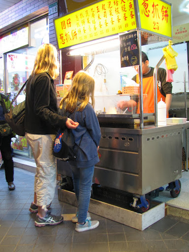 Taipei with Kids: Zoey and Logan buying an onion pancake on the street