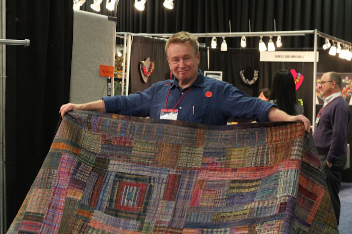 man holding up a quilt and smiling