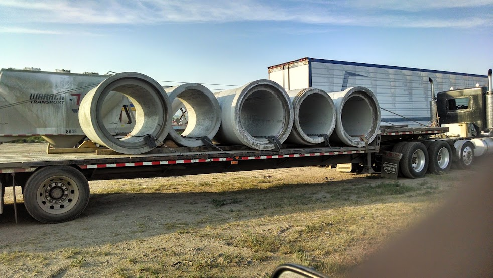 flatbed trailer loaded with big cement pipes