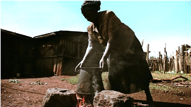 A woman in Kenya cooking with a three-stone fire