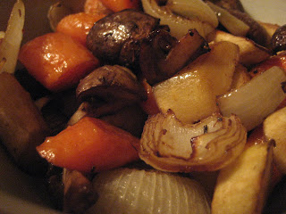 Close up photo of roasted onions, mushrooms, and carrots.