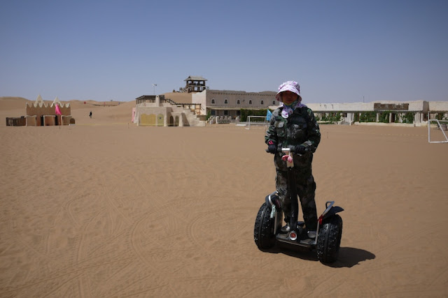 Woman riding a Segway on the sand at Shapotou in Ningxia, China