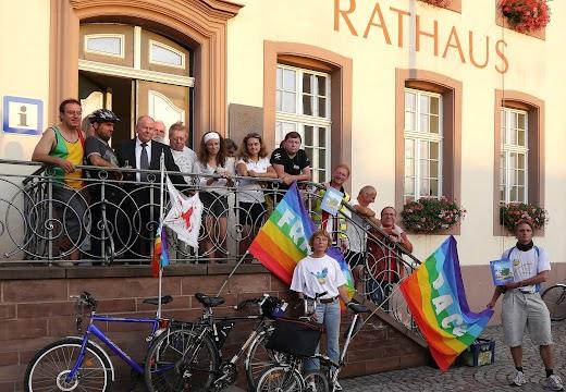 Friedensradfahrer auf der Freitreppe des Rathauses zusammen mit dem Bürgermeister, Fahrräder und Regenbogen-Friedensfahnen.