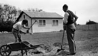 A black and white photograph of two men outside. One is digging at the ground with a pickaxe, while the other holds a shovel.