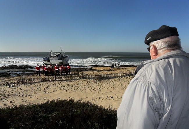 Um honem em primeiro plano a observar o barco e o conjunto de bombeiros