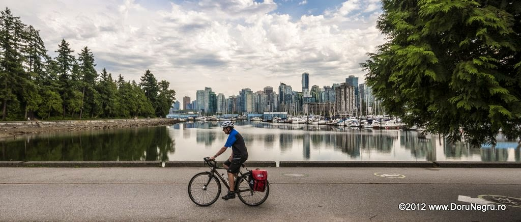 People are running, bicycling or just walking on the seawall with the city in the background
