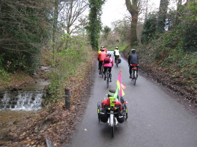 Following a group riding up hill by stream
