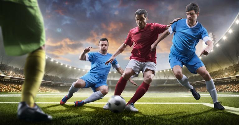 Jugadores de futbol disputando un balón en frente del portero