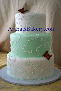 Three tier mint green and white custom unique wedding cake design with curlicues and edible butterflies