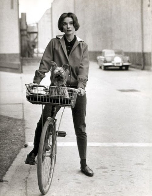 Audrey Hepburn on a bicycle with her dog