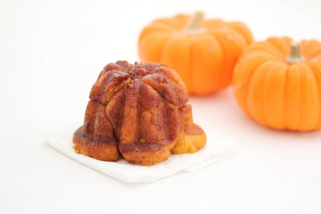 photo of one rum cake with two small pumpkins in the background