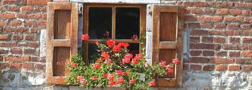 Bruselas Valonia: detalle de una ventana con flores rojas en una casa de ladrillo