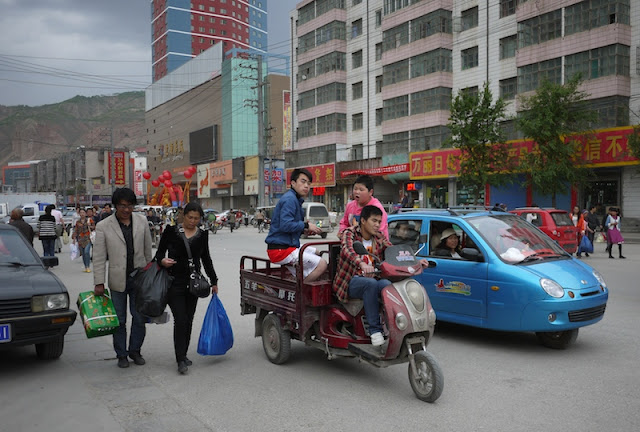 three people on a motorized tricycle cart in Xining, Qinghai, China
