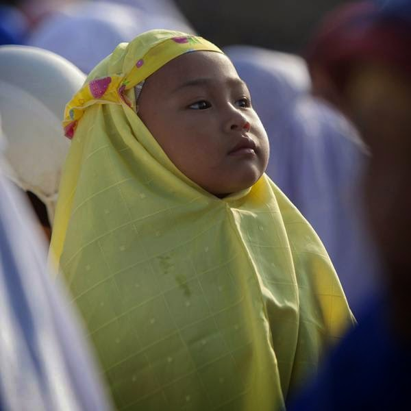 A girl attends a mass prayer during Eid-al-Fitr festival, in Kalitengah village, on the slopes of volcano Mount Merapi.