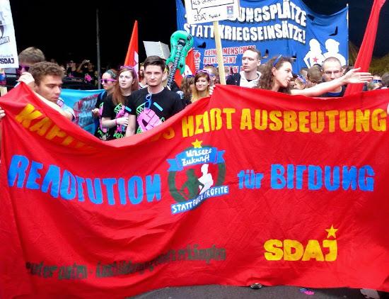 Jugendliche mit roten Fahnen und Transparenten u.a. »Kapitalismus heißt Ausbeutung«.