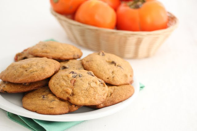 photo of a plate of cookies with persimmons in a basket in the background