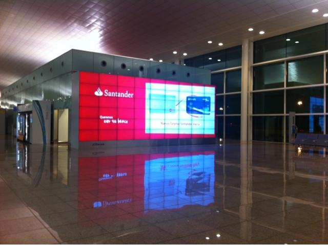 Nuevo muro digital de gran formato en el aeropuerto de for Horario oficinas banco santander barcelona