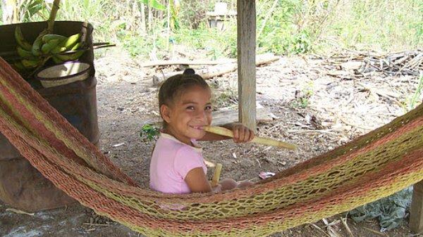 A Nuevo Paraiso girl enjoys some local sugar cane