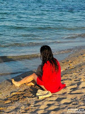 femeie in rosu la malul marii