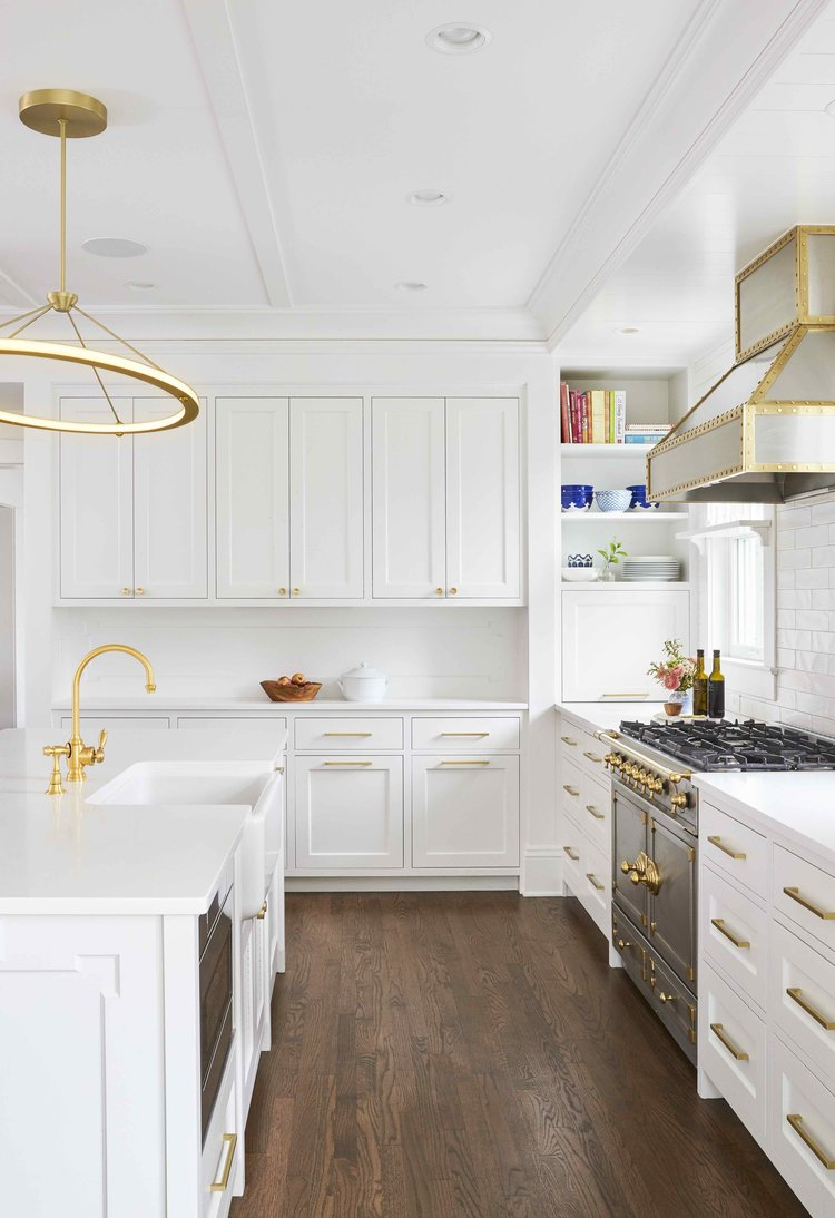 kitchen with white shaker cabinets, dark wood floors, gold cabinet hardware, gold sink and stainless steel cooking appliances with gold accents