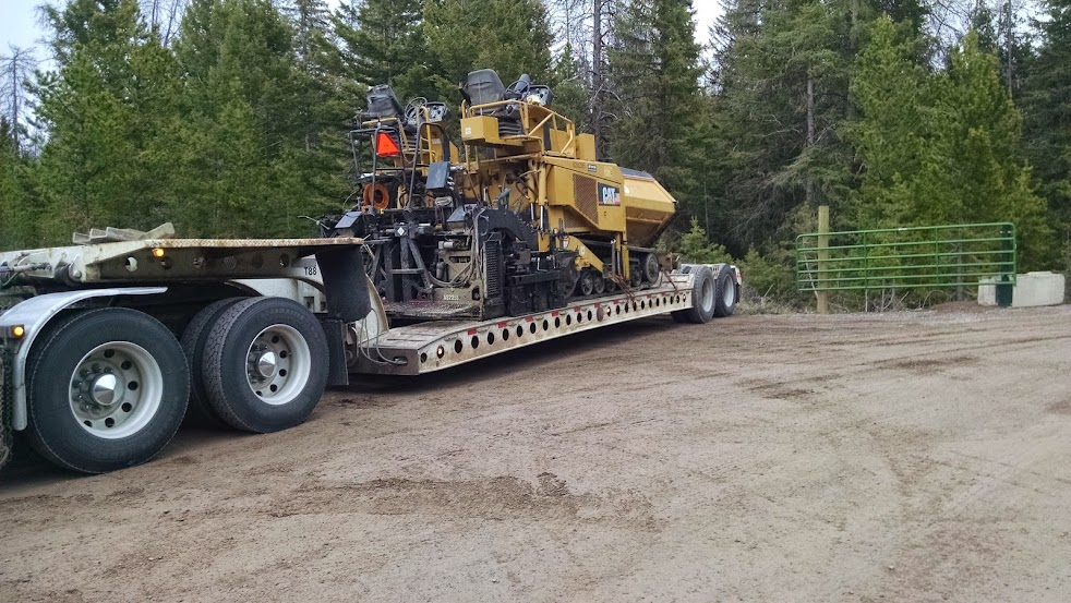 construction paver loaded on drop-deck flatbed trailer