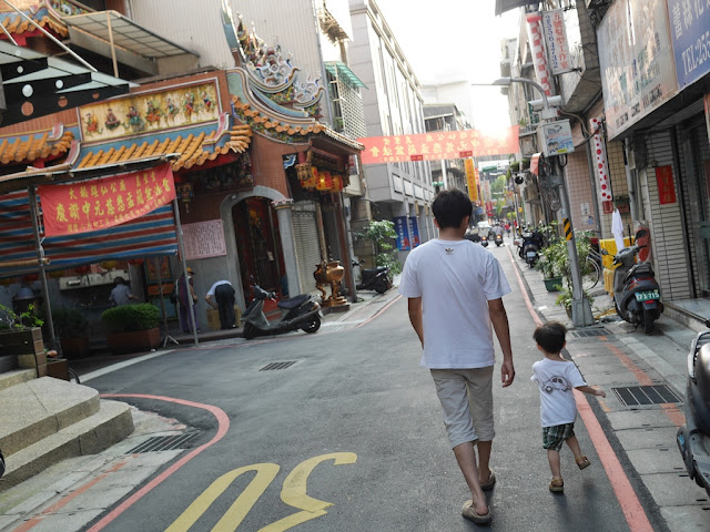 man with boy walking down an alley