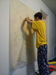 joram tracing a pattern taped to a wall