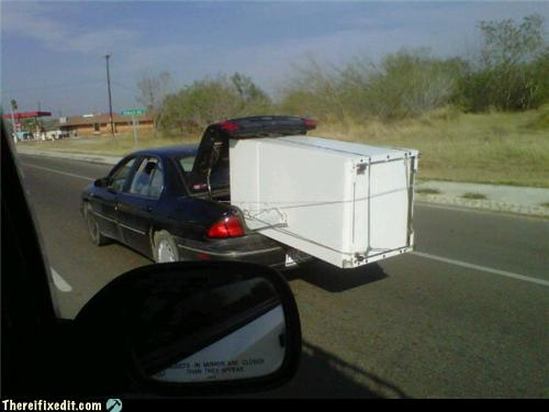 photo of a refrigerator being hauled down the freeway in a car trunk