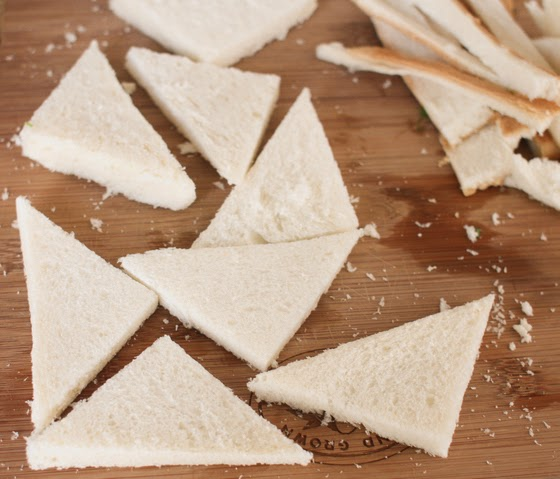 process photo showing white bread sliced into triangles with the crusts cut off
