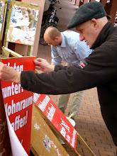 Zwei Genossen beim Überkleben der alten Plakattafeln.