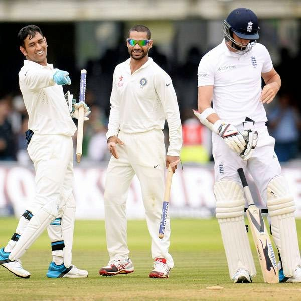India's Mahendra Singh Dhoni (L) and Shikhar Dhawan look at England's James Anderson (R) after India won the second cricket test match at Lord's cricket ground in London July 21, 2014.