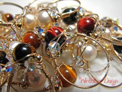 a bunch of wire wrapped sparkly rings with pearl and tiger eyes