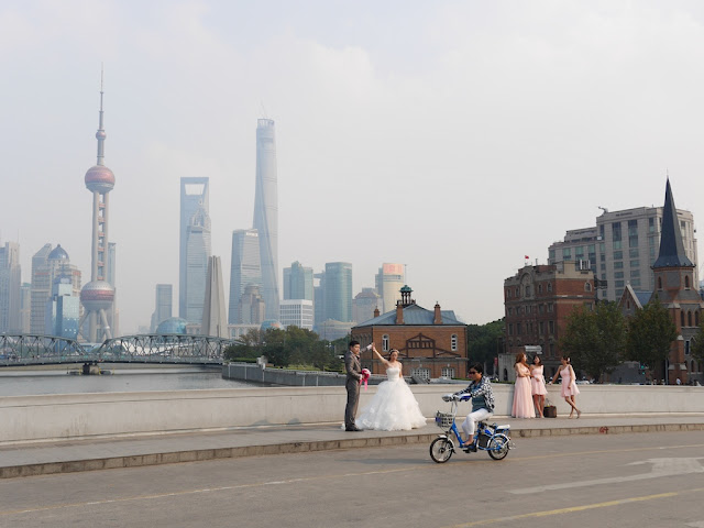posing for wedding photos with Shanghai skyscrapers in the background and a woman on an electric bike passing in front
