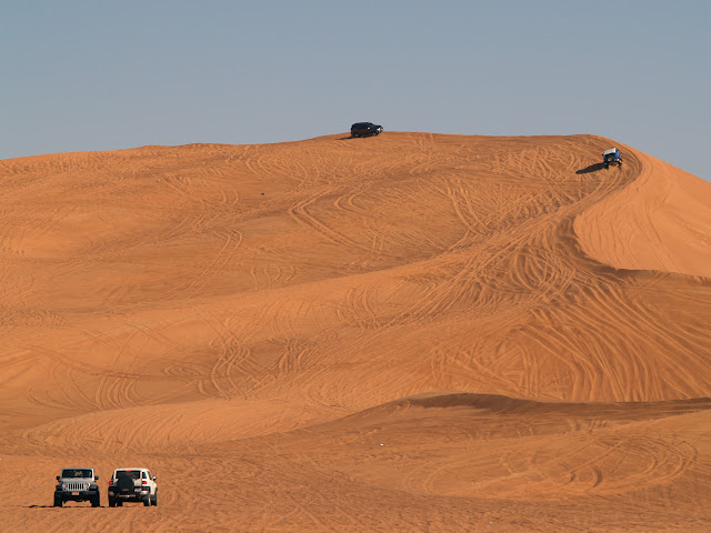 Off-road cars drive up and down large sand dune.