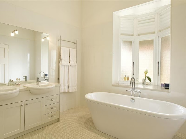 A modern take on an Edwardian bathroom, with bay window casements and built-in vanity unit. The loo is banished to a separate room