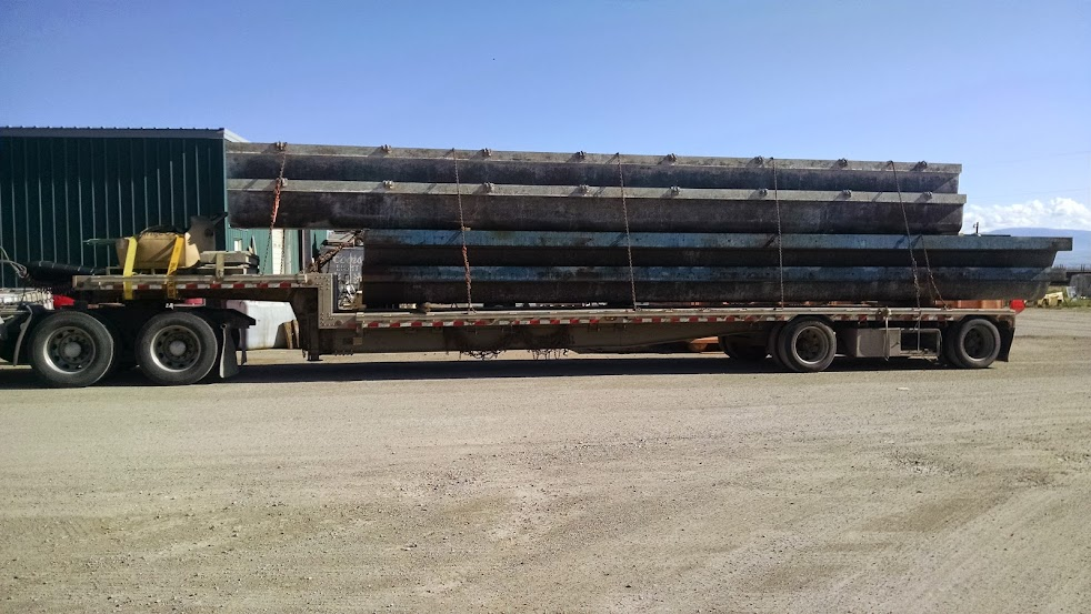 trucking flatbed trailer loaded with bridge beams