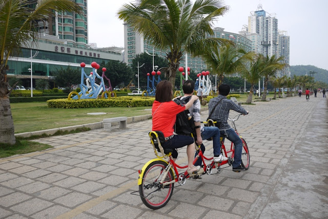three people riding a triple tandem bicycle and an artistic display of bicycle riders nearby in Zhuhai, China