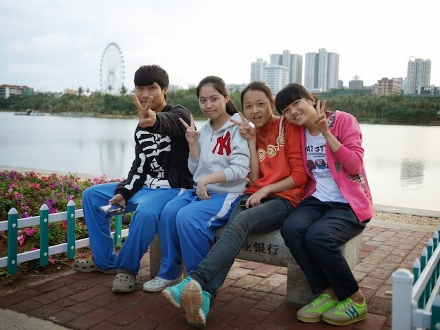 four high school students sitting on a bench with a lake and a ferris wheel in the background in Zhanjiang