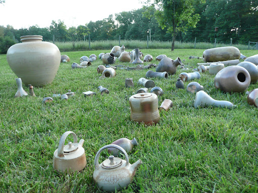 Several people put pots in the kiln, and take a turn working the firing.