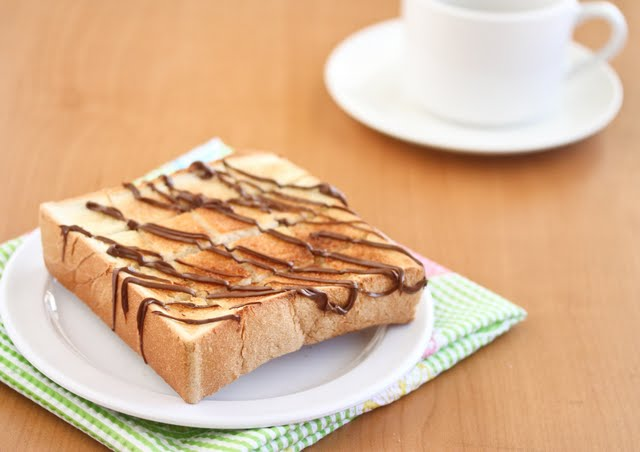 a slice of brick toast drizzled with chocolate on a white plate