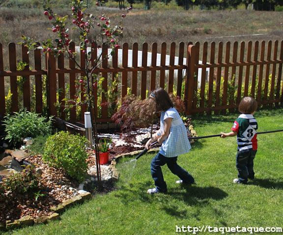 Paola y Borja regando las plantas del jardín de mis cuñados (Santiago de Compostela)