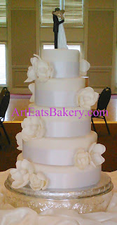 Five tier round unique custom elegant romantic wedding cake design with white sugar magnolias and Bride and Groom topper