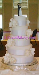 Five tier round unique custom elegant romantic wedding cake design with white sugar magnolias and Bride and Groom topper